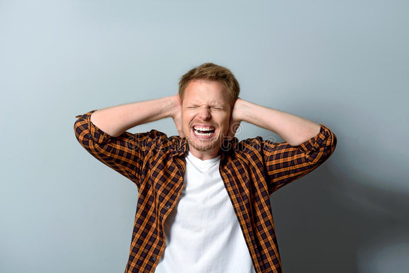 Stressed young male having painful headache stock image