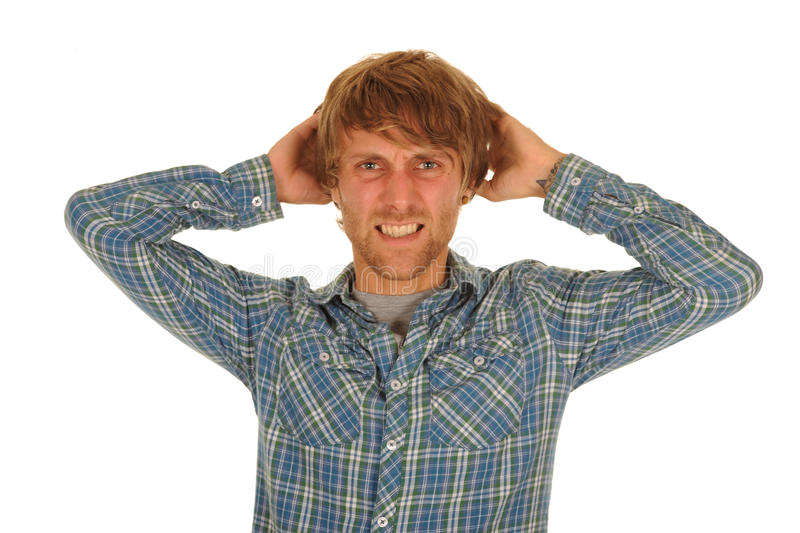 Stressed young man. Half body portrait of stressed young man in blue check shirt scratching head or pulling hair; isolated on white background royalty free stock photography