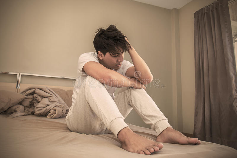 Stressed young man on his bed stock image