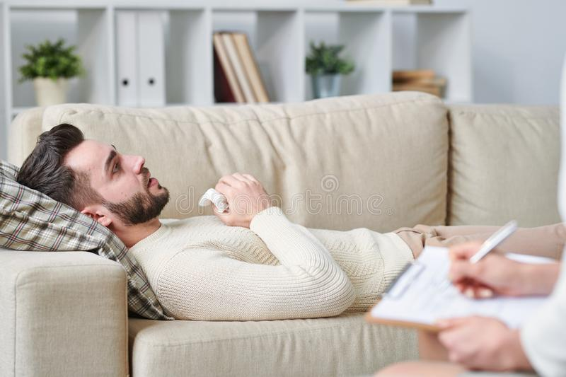 Man on couch. Stressed young man lying on couch in front of counselor and speaking about his problems at work or in family royalty free stock photo