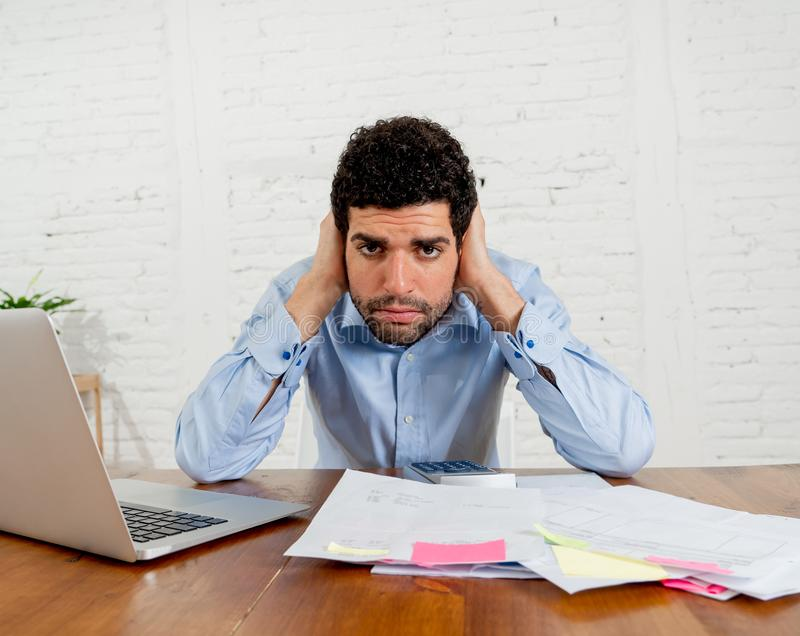 Stressed young man paying bills trying to manage home and business finances. Young entrepreneur small business owner paying bills and investment expenses having royalty free stock photo