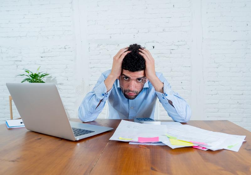 Stressed young man paying bills trying to manage home and business finances. Young entrepreneur small business owner paying bills and investment expenses having stock images