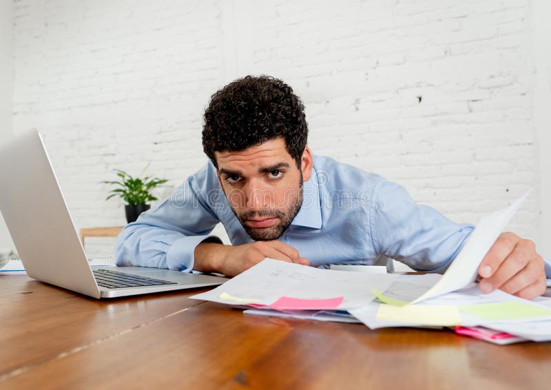 Stressed young man paying bills trying to manage home and business finances. Young entrepreneur small business owner paying bills and investment expenses having royalty free stock photos