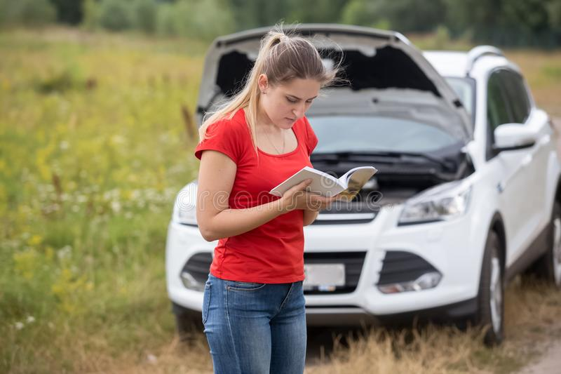 Portrait of stressed young woman with broken car reading manual. Stressed young woman with broken car reading manual royalty free stock image