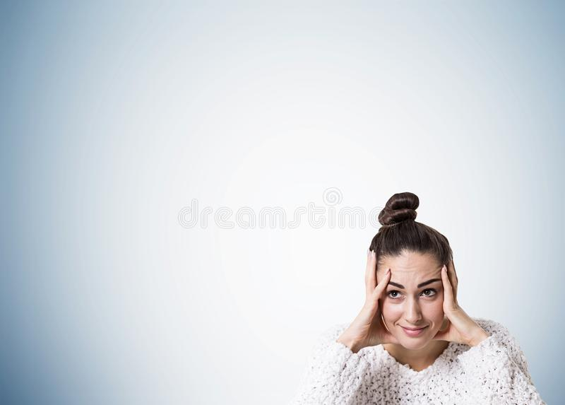 Stressed young woman with a bun, gray royalty free stock photo