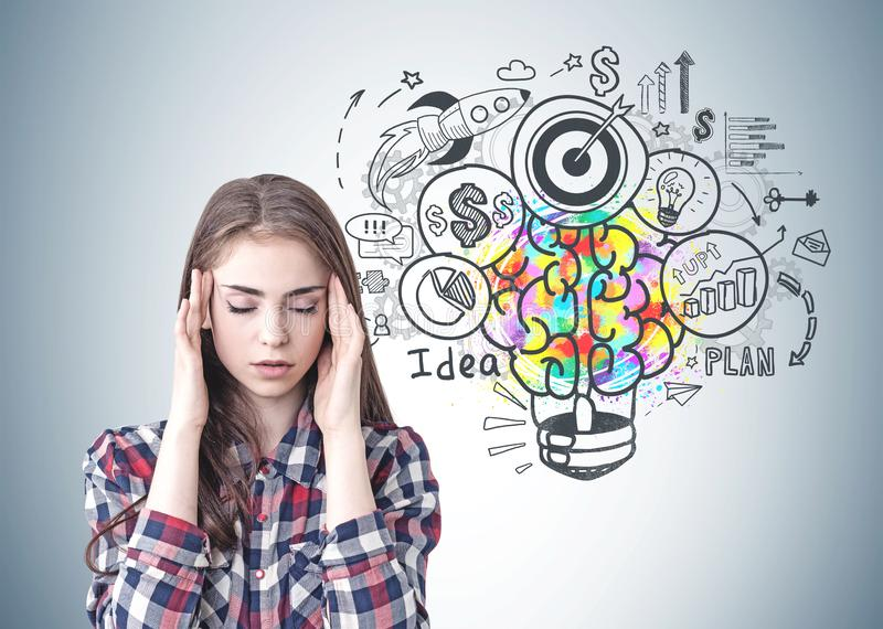 Stressed young woman, business idea. Portrait of stressed young woman wearing checkered shirt and having a headache sitting near gray wall with colorful business royalty free stock image
