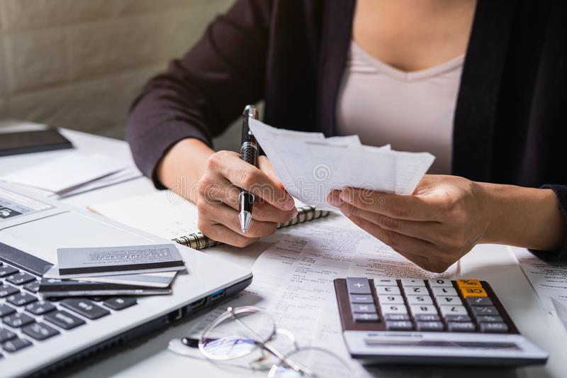 Stressed young woman checking bills, taxes, bank account balance and calculating expenses in the living room royalty free stock photos
