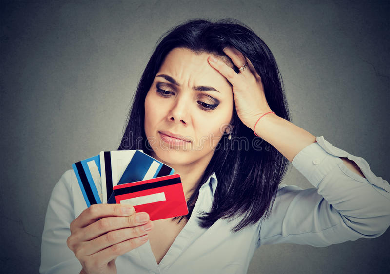 Stressed young woman in debt holding at multiple credit cards royalty free stock photo