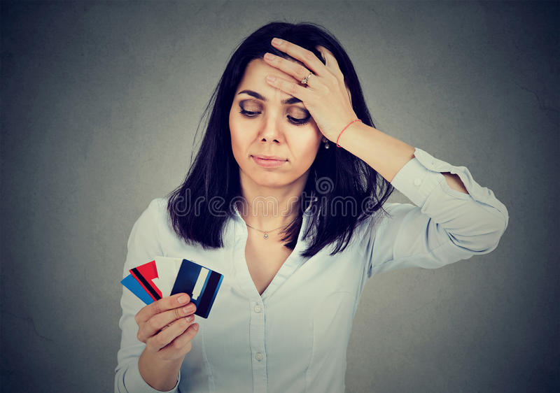 Stressed young woman in debt holding multiple credit cards royalty free stock images