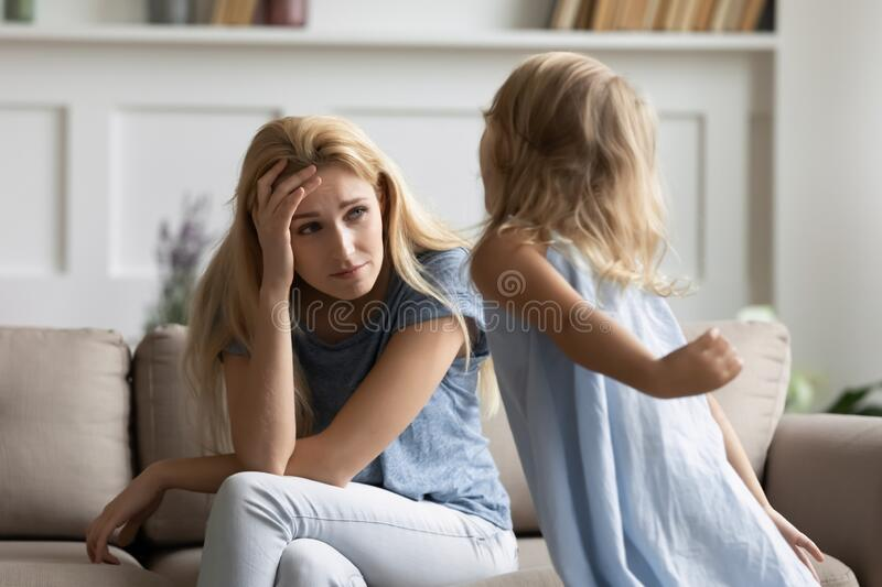 Stressed young woman irritated by loud hyperactive little preschool kid. royalty free stock photography