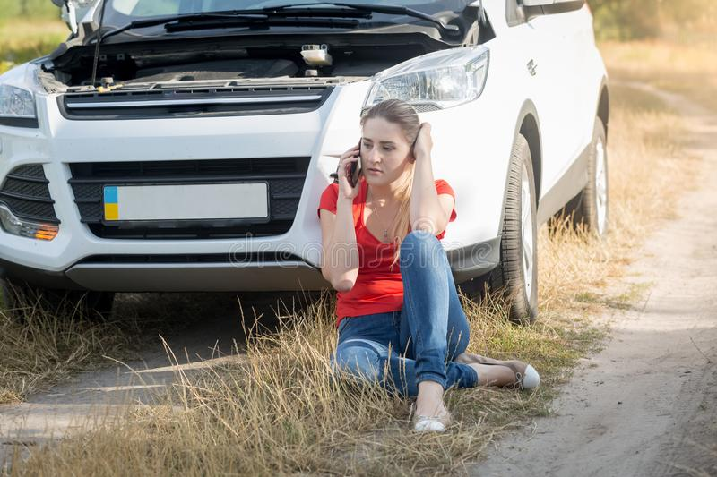 Stressed young woman leaning on broken car in field calling service for help stock images
