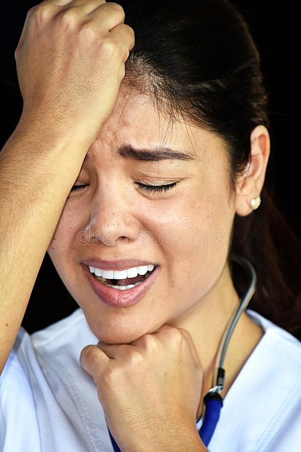 Stressful Female Nurse Wearing Scrubs. A pretty young Colombian adult female stock images