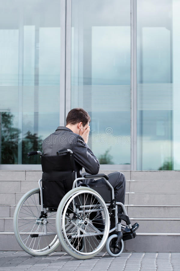 Stressful man on wheelchair before work stock photography