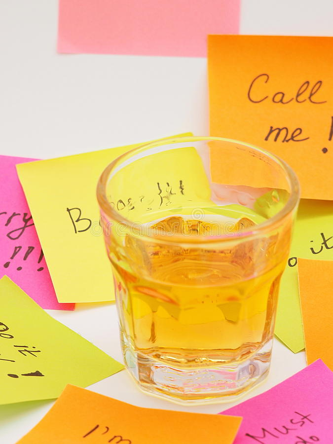 Stressful Note papers and alcohol. Colorful note papers with stressful work instructions surrounding a glass of hard alcohol royalty free stock photo