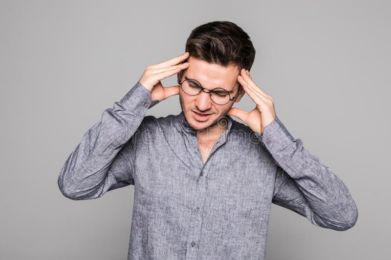 Stressful young man feels terrible headache, being frustrated and depressed, clenches teeth in pain, suffers from ache, closes royalty free stock image