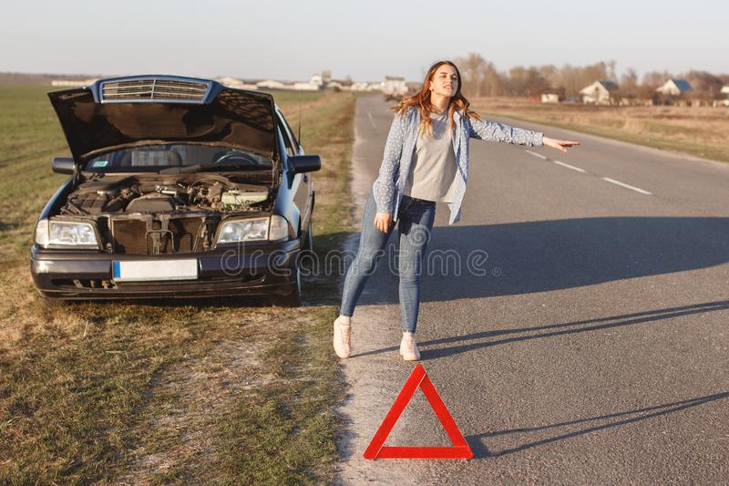 Stressful young woman driver hitchhikes and stops cars, asks for help as have problem with brocken car, uses red triangle sign to royalty free stock photo