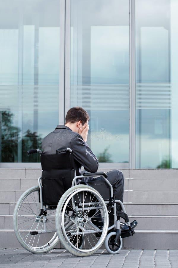 Stressig man på rullstolen för arbete arkivbild