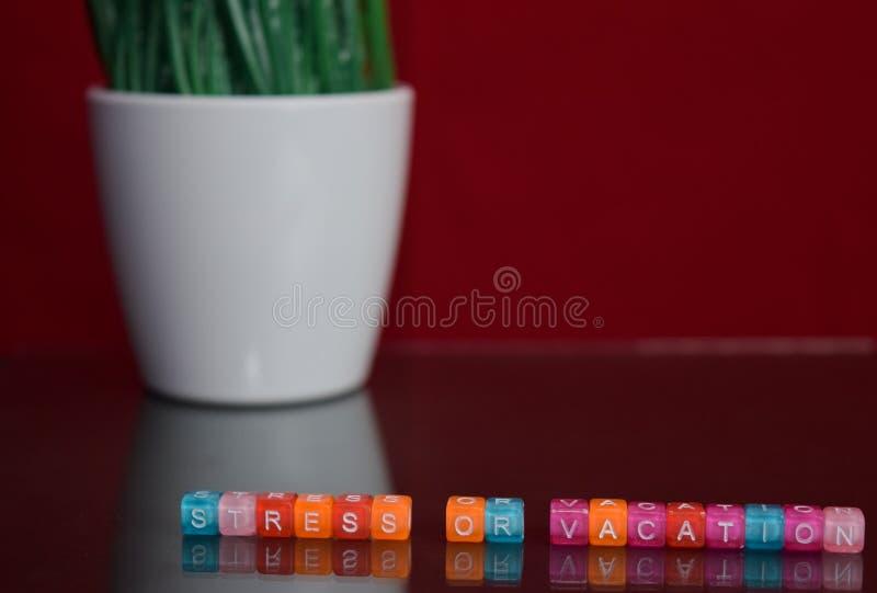 Stresu lub wakacje tekst przy kolorowym drewnianym blokiem na czerwonym tle Biurka biuro i edukacji pojęcie fotografia stock