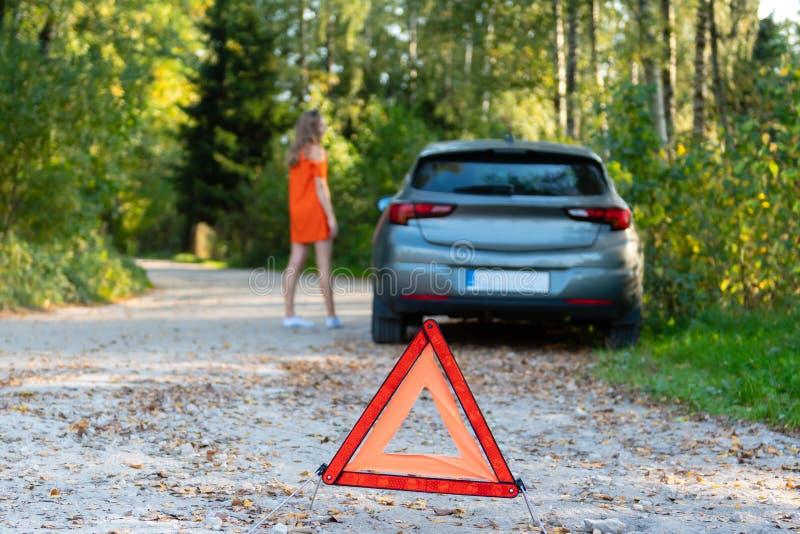 Stresujący młoda kobieta kierowca hitchhikes samochody i zatrzymuje, pyta dla pomocy jak problem z brocken samochód, używa czerwo fotografia stock
