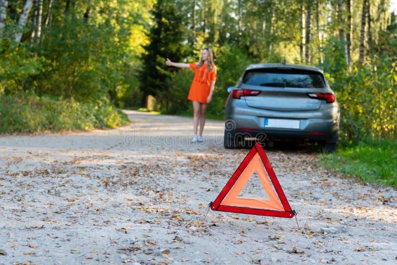 Stresujący młoda kobieta kierowca hitchhikes samochody i zatrzymuje, pyta dla pomocy jak problem z brocken samochód, używa czerwo fotografia royalty free