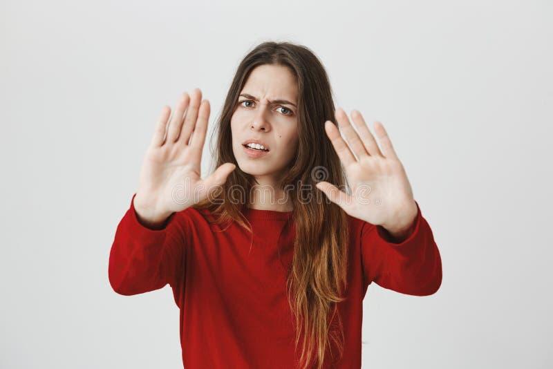 Stresująca się out agresywna gniewna młoda kobieta z prostym ciemnym włosy, marszczący brwi w obmierzłości, utrzymuje ręki w prze zdjęcia stock