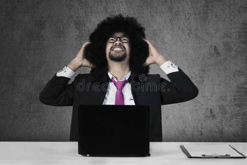 Stresujący Afro biznesmen trzyma jego głowę zdjęcie stock