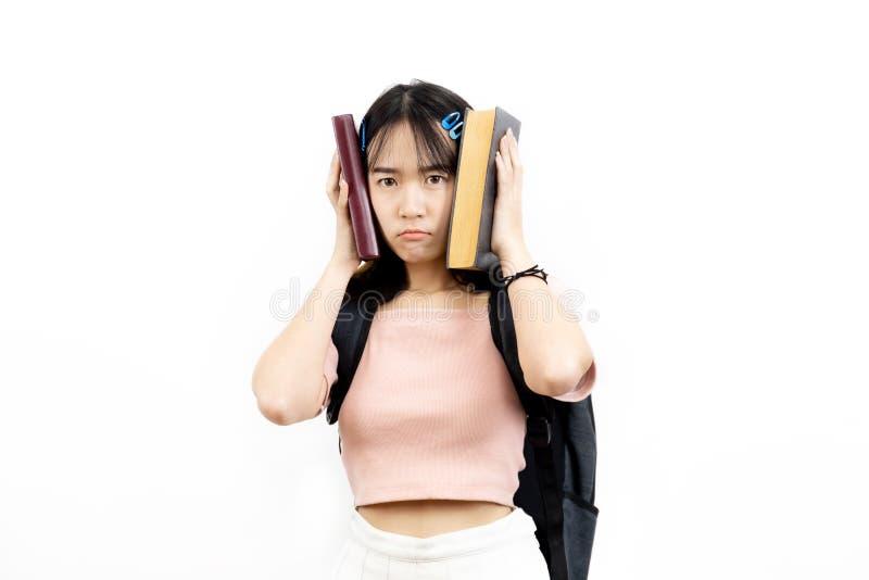 Stresujący i wzburzeni Azjatyccy żeńscy student collegu trzyma stos książki z torbą odizolowywającą nad białym tłem zdjęcie royalty free