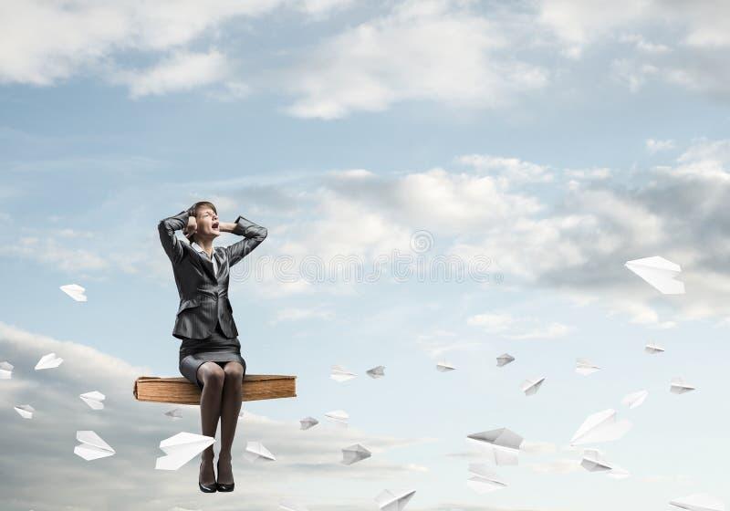 Stresujący kobiety obsiadanie na obsiadaniu na dużej książce obrazy royalty free