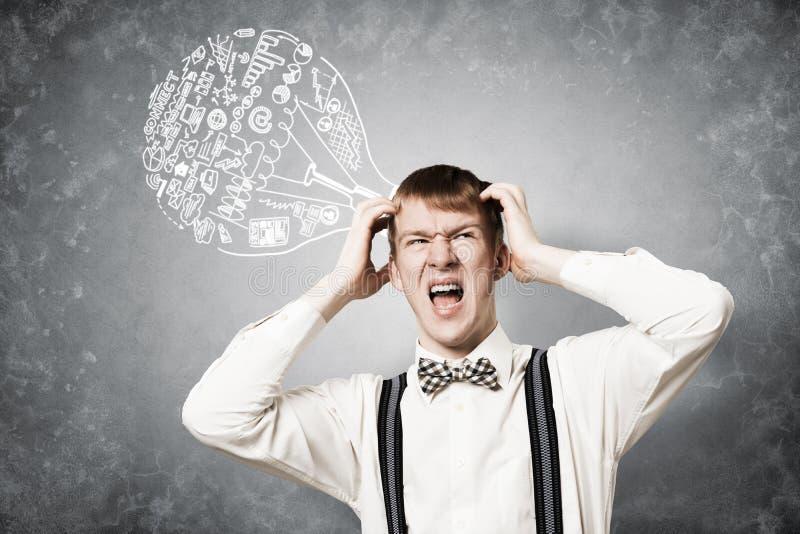 Stresuj?ce rudzielec ucznia utrzyma? r?ki na g?owie zdjęcie stock