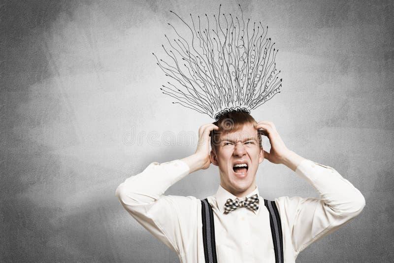 Stresuj?ce rudzielec ucznia utrzyma? r?ki na g?owie fotografia royalty free