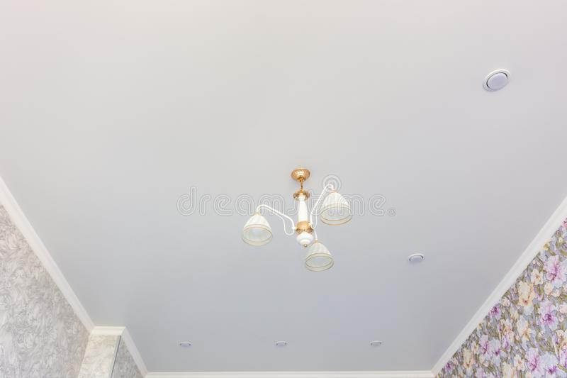 Stretch matte ceiling in the room with a chandelier and spotlights, with natural light. Stretch matte ceiling in the room with a chandelier and spotlights, with royalty free stock photos