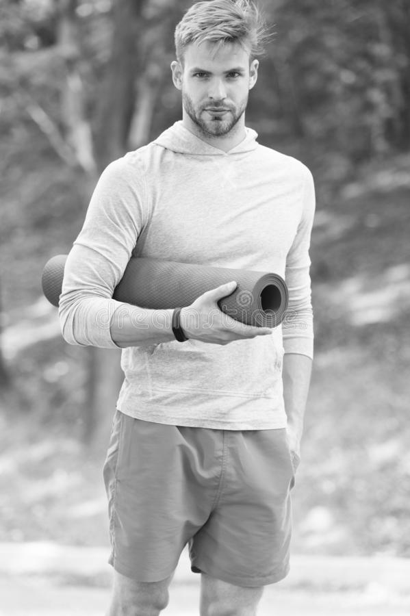 Stretch muscles pilates practise. Sportsman carries yoga mat for outdoor exercises. Outdoor yoga concept. Man athlete. Calm face carries mat for stretching royalty free stock photo