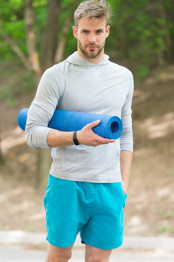 Stretch muscles pilates practise. Sportsman carries yoga mat for outdoor exercises. Outdoor yoga concept. Man athlete. Calm face carries mat for stretching royalty free stock photos