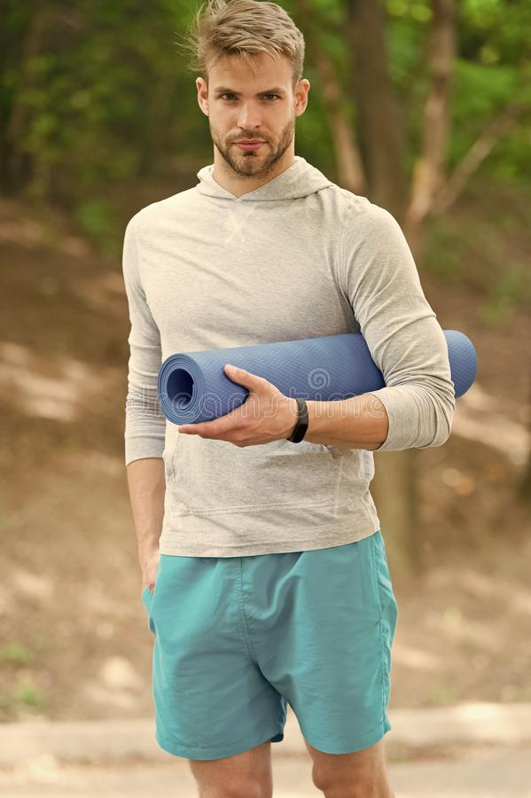 Stretch muscles pilates practise. Sportsman carries yoga mat for outdoor exercises. Outdoor yoga concept. Man athlete stock photos