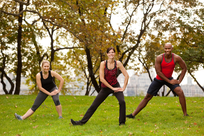 Stretch Park. A group of people stretching in a park - focus on front woman stock images