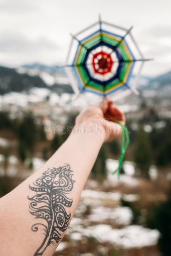Stretched hand with henna tattoo holding knitted mandala. Stretched female hand covered with henna feather tattoo holding knitted mandala up in the air, on a royalty free stock photography