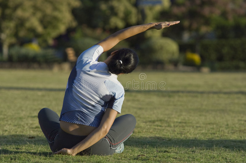Stretching. Woman stretching in late afternoon light royalty free stock photos