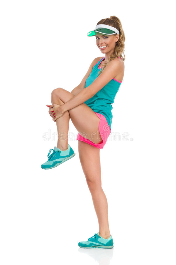 Stretching Buttocks Exercise. Young woman in pink shorts and turquoise shirt standing on one leg, holding his other leg knee and stretching gluteus maximus. Side stock photos