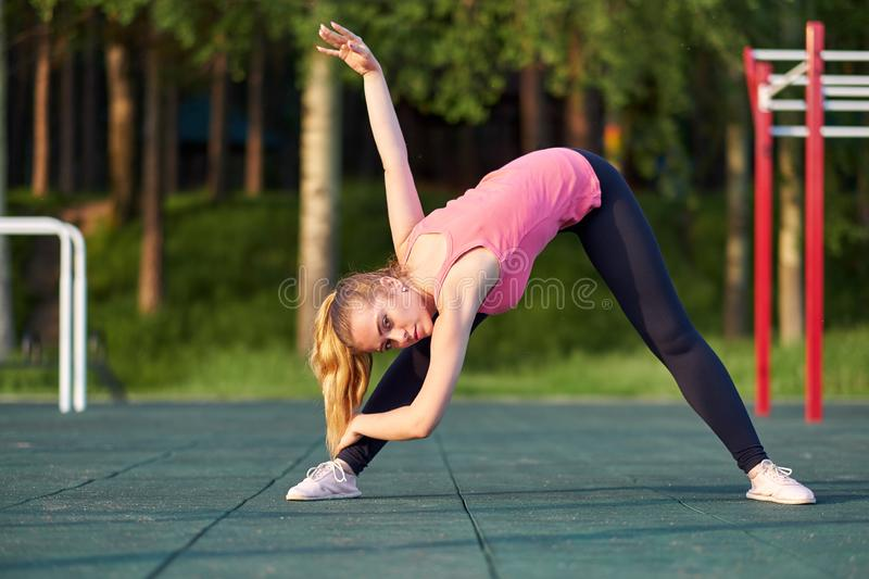 Stretching danser or gymnast woman training in workout sports ground.  stock photography