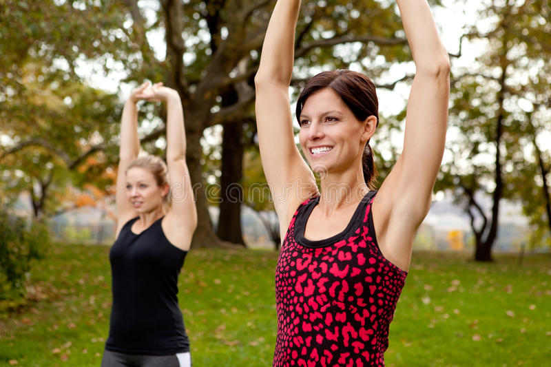 Stretching Exercise. Two women stretching in a park - outdoor exercise stock photography