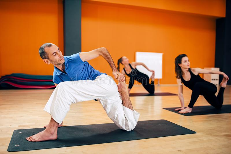 Stretching exercise, female yoga group in action. Training with instructor, workout in gym. Yogi indoor royalty free stock photography