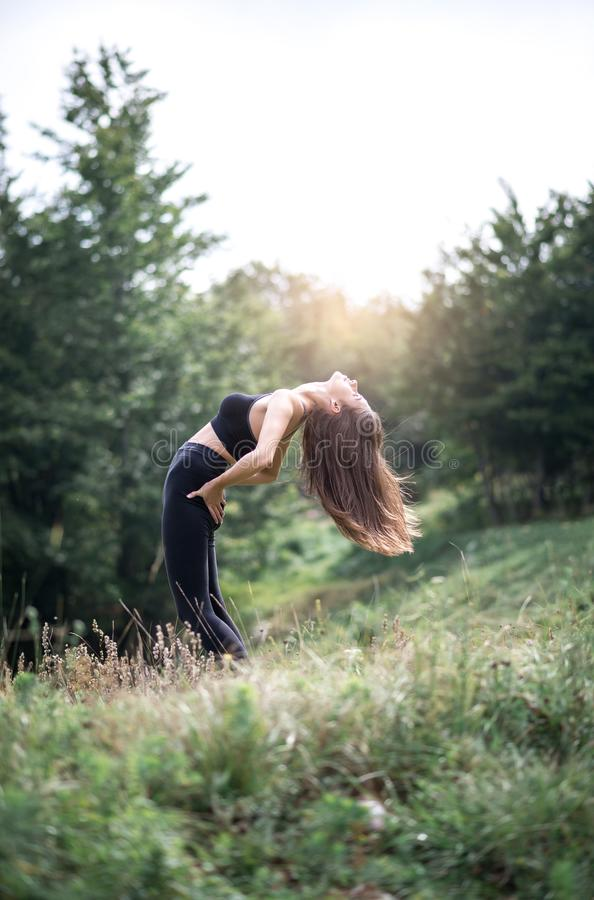 Stretching exercises in nature. Young attractive woman doing stretching exercise in nature during morning hours. Toned image royalty free stock photography
