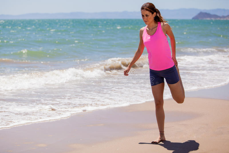 Stretching before going for a run. Young Latin woman doing some stretching exercises before running by the beach stock image