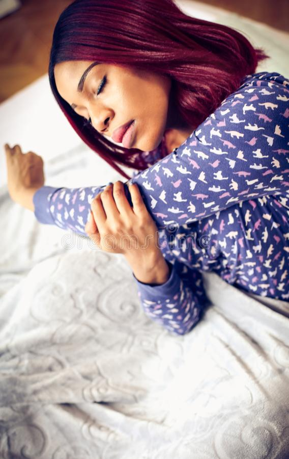 Stretching is good for beauty morning. African American woman having exercise in bed. Space for copy royalty free stock photos