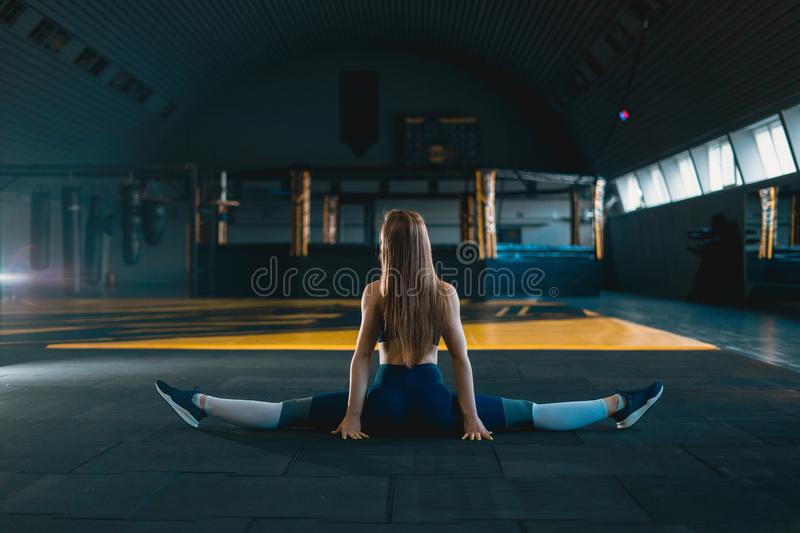 Stretching gymnast girl doing vertical split, twine. Side view of attractive young woman doing core exercise. At crossfit gym stock photos