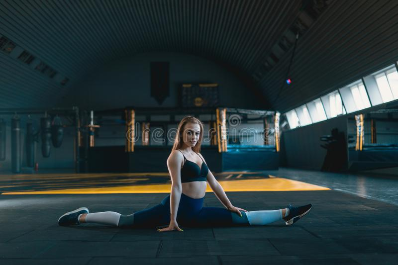 Stretching gymnast girl doing vertical split, twine. Side view of attractive young woman doing core exercise. At crossfit gym royalty free stock photography