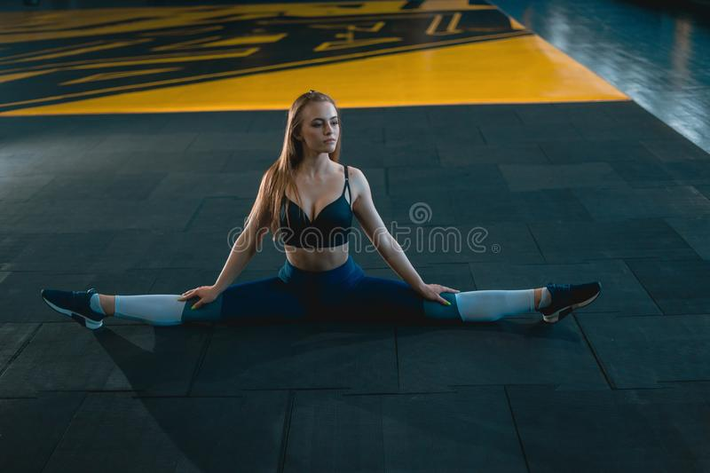 Stretching gymnast girl doing vertical split, twine. Side view of attractive young woman doing core exercise. At crossfit gym stock image