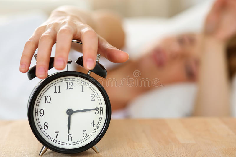 Stretching hand of sleepy young woman trying kill alarm clock. Ringing awakening early morning. Early wake up, not getting enough sleep, getting work concept stock photography