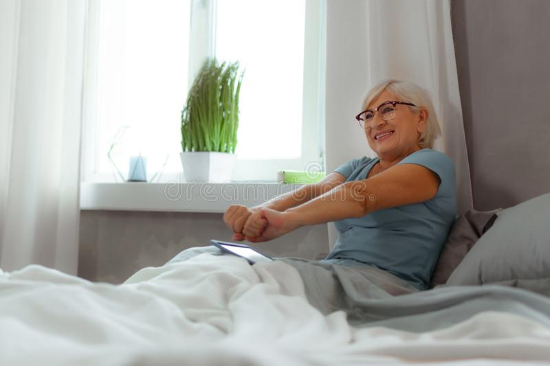 Active elderly female stretching her arms after sleeping royalty free stock photos