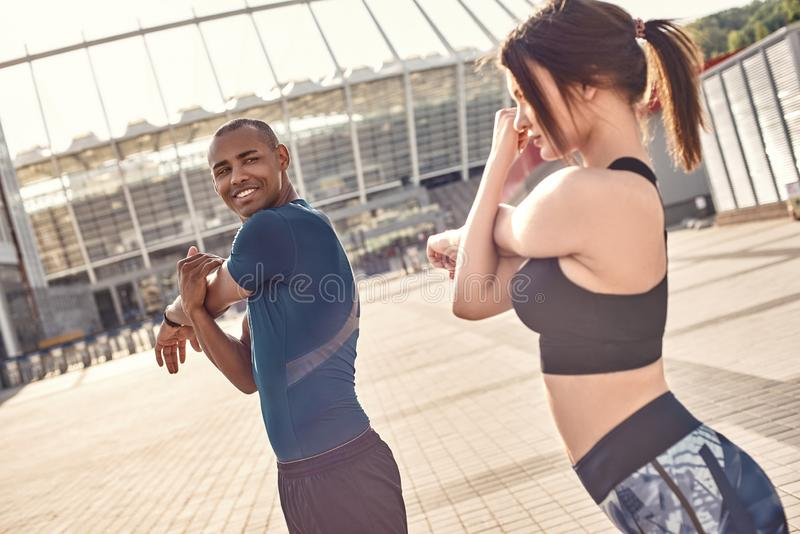 Stretching together. Side view of sporty and cheerful couple standing outside,stretching and warming up before training royalty free stock image